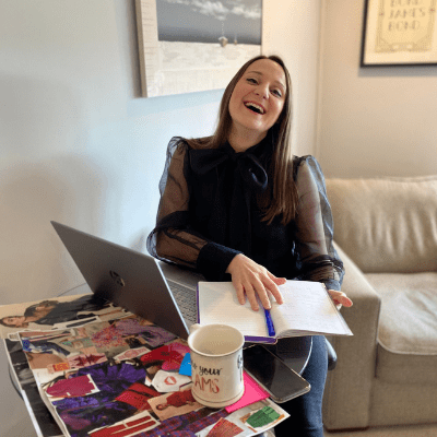 Lucy Grimwade at a table with notebook, laptop, magazines and mug